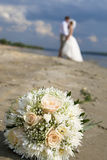 Wedding bouquet of roses on the beach. (foreground), the bride and groom on the background Stock Image