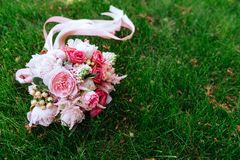 Wedding bouquet of roses on green grass stock photography
