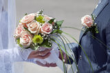 Wedding bouquet of roses and the groom's boutonniere. Wedding bouquet of roses in hand of the bride and the groom's boutonniere Stock Photo