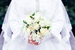 Wedding bouquet of roses in hands of the bride. Bride hands holding wedding bouquet of white roses Stock Image