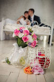 Wedding bouquet from roses and happy bride  and the cheerful groom  lie on a bed in bedroom Stock Photos
