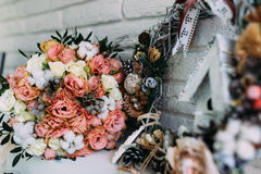 Wedding bouquet with roses in New Year interior. Beautiful details of wedding bouquet located in new year interior with small wood house Royalty Free Stock Photos