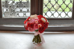 A wedding bouquet with roses placed on the front of an old classic window on a shiny marble stone.  Royalty Free Stock Images