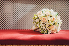 Wedding bouquet of roses on a red velvet. Wedding bouquet of roses lying on a red velvet Stock Image