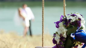 Wedding bouquet on seesaw with blurred married couple in background stock footage