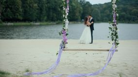 Wedding Bouquet on Seesaw with Married Couple. Wedding bouquet on seesaw with blurred married couple in background stock footage