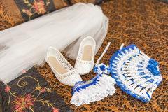 Wedding bouquet and shoes of the bride. Garter, shoes, fan, veil bride on the bed. Royalty Free Stock Image