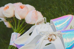 Wedding bouquet and shoes lying down on green grass Royalty Free Stock Images