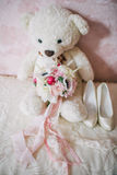 Wedding bouquet with shoes and teddy bear on the sofa Royalty Free Stock Photo