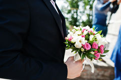 Wedding bouquet of small white and rose flowers at hand of groom Royalty Free Stock Photography