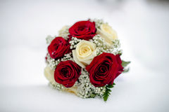 Wedding bouquet on the snow. Bridal bouquet of white and red roses lying in the snow Stock Photo