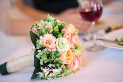 Wedding Bouquet. On a table, hands of newlyweds and a glass of wine on a background Stock Image