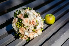 Wedding bouquet on a table. Round wedding bouquet of roses and freesias with green apple at sunny day stock photography