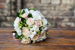 Wedding bouquet on a table. Round wedding bouquet of roses and freesias on the table royalty free stock photo