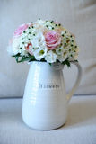 Wedding bouquet in a vase. Vertical shot of pretty garden flowers wedding bouquet arranged into a white vase with Flowers label Stock Photo