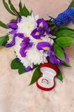 Wedding bouquet with violet iris and chrysanthemum near golden r Royalty Free Stock Photography