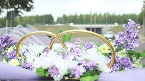Wedding bouquet of violet purple flowers blowing on wind on riding car, happy just married couple stock video footage