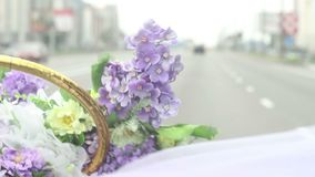 Wedding bouquet of violet purple flowers blowing on wind on riding car, happy just married couple stock footage