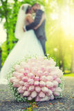 Wedding bouquet. Wedding bouquet lying on the ground in the park and in the background of a young couple in a romantic embrace Stock Photos