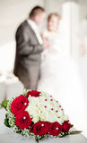 Wedding bouquet with the wedding couple in the bac stock photo