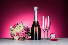 Wedding bouquet, wedding rings and champagne on table. On pink stock photo