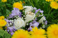 Wedding bouquet and wedding rings in dandelions. Wedding rings and Beautiful summer wedding bouquet of white roses and purple rocuses in dandelions and grass Royalty Free Stock Images