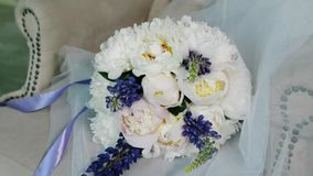 Wedding bouquet on a white armchair in a luxury photo studio. Bouquet of peonies and lupines with a purple ribbon. stock video