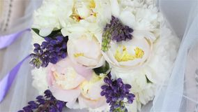 Wedding bouquet on a white armchair in a luxury photo studio. Bouquet of peonies and lupines with a purple ribbon. stock video footage
