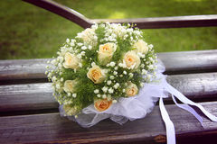 Wedding bouquet with white bow. Lying on a bench Royalty Free Stock Photos