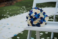 Wedding bouquet on white chair and rose petals. Wedding Aisle and white carpet strewn with rose petals also on grass. White seats for guests with bouquet of Stock Photography