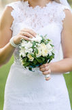 Wedding bouquet of white flowers and greenery in the hands of the bride in white dress. Wedding bouquet of white flowers and greenery in the hands of the bride Royalty Free Stock Photography