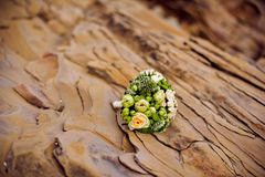 Wedding bouquet of white flowers and greenery stands near textured rocks. In the mountains Royalty Free Stock Photos