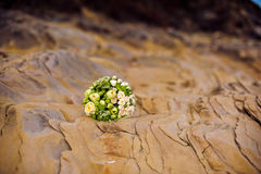 Wedding bouquet of white flowers and greenery stands near textured rocks. In the mountains Stock Photo