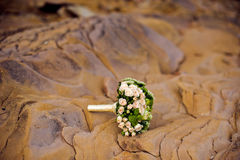 Wedding bouquet of white flowers and greenery stands near textured rocks. In the mountains Royalty Free Stock Images