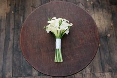 A wedding bouquet of white flowers lies on a round table. Beautiful wedding bouquet. Bouquet of white calla for the bride on the wedding day Royalty Free Stock Photos