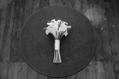A wedding bouquet of white flowers lies on a round table. Beautiful wedding bouquet. Bouquet of white calla for the bride on the wedding day Stock Photos