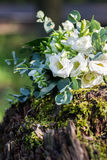 Wedding bouquet of white flowers on the wood stump outdoors. Close view Royalty Free Stock Image