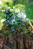 Wedding bouquet of white flowers on the wood stump outdoors , close view.  Stock Photography