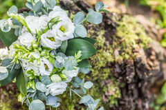 Wedding bouquet of white flowers on the wood stump outdoors. Top view Royalty Free Stock Photo
