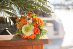 Wedding bouquet from white, orange flowers, roses lies under a p. Alm tree near yacht, sunset and port on wooden bench stock photography