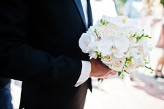 Wedding bouquet of white orchids on hand of groom.  Royalty Free Stock Photos