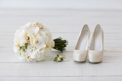Wedding bouquet of white orchids and shoes.  Royalty Free Stock Image