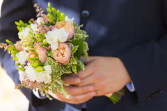 Wedding bouquet of white and pale pink flowers in hands of groom. Wearing dark blue wedding suit Stock Image