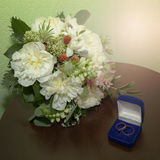 Wedding bouquet of white peonies and rings in a box Royalty Free Stock Photo