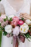 Wedding bouquet with white and pink rose, peonies and greenery standing in bride hands on white lace dress background Stock Photography