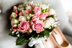 Bride`s shoes and a bouquet of flowers stock images