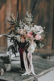 Wedding bouquet with white and pink roses and other flowers on a rustic table. Artwork. Indoors. Vertical Stock Images