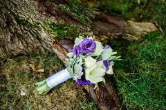 Wedding bouquet of white and purple flowers. Under the tree Royalty Free Stock Image
