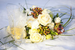 Wedding bouquet of white and red flowers and two glasses of champagne on snow. In winter Stock Images