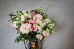 Wedding bouquet of white, red and pink flowers in a vintage vase. Stands on a light background. White and pink roses. Morning bride, copyspace Royalty Free Stock Images
